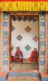 Timbu, Bhután - 15 de septiembre de 2016: Dos monjes que se sientan en el cuarto en Simtokha Dzong, Timbu, Bhután fotografía de archivo libre de regalías