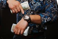 Time är pengar Begreppet av tid och pengar En man som rymmer mycket pengar och, visar upp i rätt tid Royaltyfri Foto