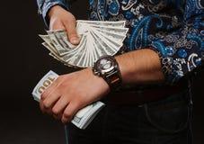 Time är pengar Begreppet av tid och pengar En man som rymmer mycket pengar och, visar upp i rätt tid Royaltyfri Fotografi