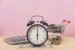 Time är pengar ringklocka och dollar, mynt på tabellen Arkivfoton