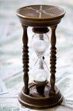 Time är pengar Timglas och oss dollar Arkivfoto