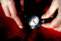 Time 1. Two hands holding a watch with a red scarf for a background stock photos
