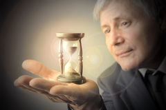 Time. Closeup of Old businessman holding hourglass Stock Photography