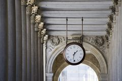 Time. Clock in the ancient colonnade Stock Photography