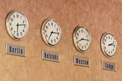 Time. Four clocks, showing the time in different cities of the world on the wall Royalty Free Stock Photos