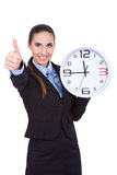 On time. Businesswoman holding clock and shoving sign OK Royalty Free Stock Photos