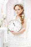 Time. Beautiful little girl in white dress holding clocks Royalty Free Stock Photography