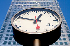 Time. A street clkock in front of a skyscraper office building Royalty Free Stock Image