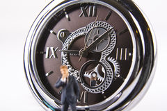 Is it time. Miniature businessman with watch in background Stock Image
