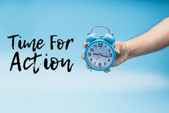 Time for Action and a Hand Holding a blue Analog Alarm Clock. Up communication symbol down deadline clean exercise care start clear easy change challenge switch stock images