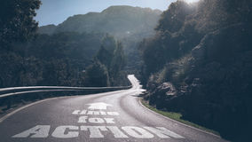Time for action. Long deserted road through mountains with concept words time for action and arrow on asphalt Royalty Free Stock Image