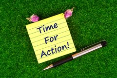 Time for action. In sticky note with pen and dried rose buds on grass Stock Photography