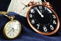 Time & Again. Skewed view of two clocks and a pocket watch in a still life image Royalty Free Stock Photos