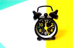 Vintage black alarm clock on multicolored background royalty free stock photography