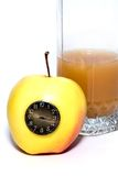 Time of apple diet. Glass of juice behind the yellow apple with the clock Royalty Free Stock Image