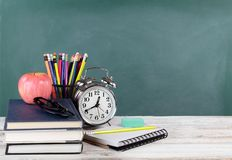 Time for back to school concept including books and stationery supplies with green chalkboard in background royalty free stock photography