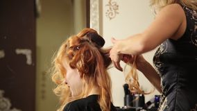 Time in a beauty salon. Young woman in a beauty salon, hairdresser doing hairstyle with curls to beautiful model stock video