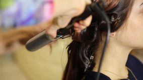 Time in a beauty salon. Young woman in a beauty salon, hairdresser doing hairstyle to beautiful model stock video