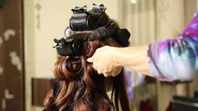 Time in a beauty salon. Young woman in a beauty salon, hairdresser doing hairstyle to beautiful model stock video footage