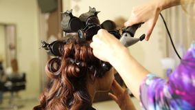 Time in a beauty salon. Young woman in a beauty salon, hairdresser doing hairstyle to beautiful model stock footage