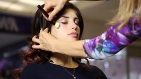 Time in a beauty salon. Young woman in a beauty salon. Stylist makes makeup bride on the wedding day. cosmetic powder stock video