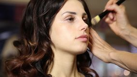 Time in a beauty salon. Young woman in a beauty salon. Stylist makes makeup bride on the wedding day. cosmetic powder stock video footage
