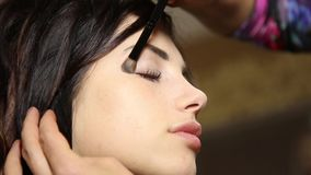 Time in a beauty salon. Young woman in a beauty salon. Stylist makes makeup bride on the wedding day. cosmetic powder stock footage