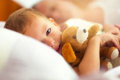 Time for bed! The little boy lying in bed, hugging a toy Royalty Free Stock Photos