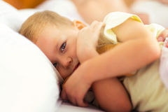 Time for bed! The little boy lying in bed, hugging a toy Stock Photography