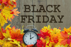 Time for Black Friday Shopping. Autumn Leaves and Alarm Clock with grunge wood with text Black Friday Stock Photo