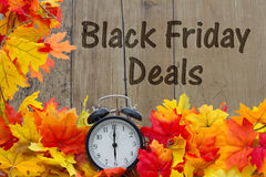 Time for Black Friday Shopping Deals. Autumn Leaves and Alarm Clock with grunge wood with text Black Friday Deals Royalty Free Stock Photo