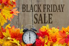 Time for Black Friday Shopping Sale. Autumn Leaves and Alarm Clock with grunge wood with text Black Friday Sale Stock Photo