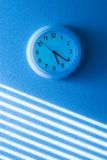 Time blue clock. Blue wall clock time light Royalty Free Stock Photography