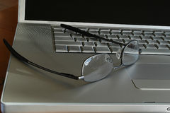 Time for a Break. Silver laptop with spectacles on keyboard Stock Images