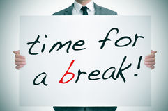 Time for a break. Businessman holding a signboard with the text time for a break written in it Stock Photography