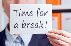 Time for a break - Businesswoman with sign in the office. Time for a break - Businesswoman holding sign with text in the office Stock Photography