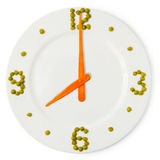 Time of breakfast, �lock from plate, carrots and green peas Royalty Free Stock Photography