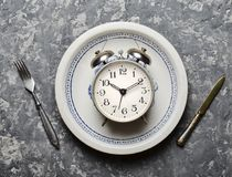 Time for breakfast. Alarm clock in a plate, fork and knife on a concrete table. Top view. Flat lay.  Stock Photography