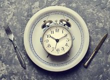 Time for breakfast. Alarm clock in a plate, fork and knife. On a concrete table. Top view. Flat lay Stock Image