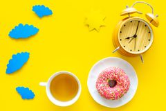 Time for breakfast concept. Tea, donut near alarm clock, sun and clouds cutout on yellow background top view copy space stock image