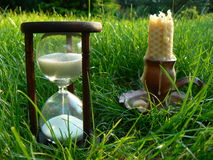 Time is burning. Scene with sandglass and candle Royalty Free Stock Image