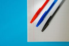 Blue, red and black fountain pens lie on the notebook stock photography