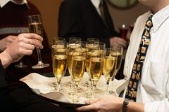 Time for Champagne. Waiter serving some glasses of champagne stock image