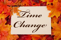 Time Change. A Time Change card, A beige card with words Time Change over red and orange maple leaf background Stock Photography