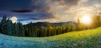 Time change concept above alpine forest glade. Panorama of time change concept above alpine forest glade with sun and moon. beautiful early autumn landscape in Stock Image