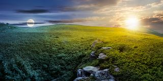 Time change concept over panoramic landscape. Time change concept with sun and moon over panoramic landscape. lovely summer scenery with boulders among the grass Stock Photos
