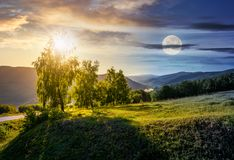 Time change concept in mountains. Time change concept over the trees on grassy hill in mountains. lovely nature scenery with sun and moon Stock Photography