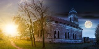 Abandoned catholic church on hill. Time change concept with sun and moon. panorama of abandoned catholic church on hill stock photo