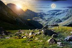 Time change concept in Transfagarasan valley. Rocks on grassy meadow and slopes lit by sun and moon simultaneously. half of the valley in shade of mountain stock photos