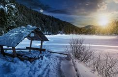 Time change concept in winter forest. Day and night time change concept in winter spruce forest with wooden bower. beautiful mountainous landscape near snow Stock Images